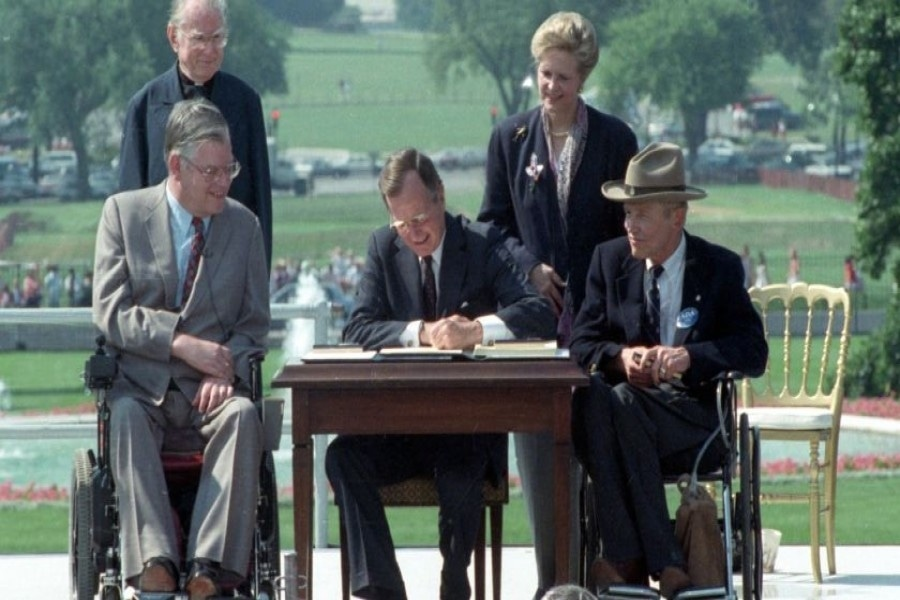 President George H. W. Bush, center, signs the Americans with Disabilities Act during a ceremony on the South Lawn of the White House on July 26, 1990. The act has been cited in an increasing number of lawsuits against businesses over the accessibility of their websites. (Barry Thumma / Associated Press)